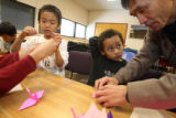 (from right to left)  Kai Omote (cq) is assisted by school teacher Mr. Machihara (cq) in...