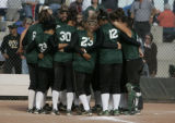 Bear Creek huddles after winning a quarterfinal 5A Girl's State Softball tournament against...
