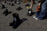 (9/01/2004) New York City-Jeanine Urbanski, 24, Brooklyn, places a flower in one of 971 boots to...