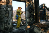 Firefighter Jay Sartoris douses hotspots inside a burned structure on Carbon Canyon Rd. in Malibu,...