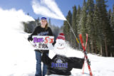 Leisa Gibson holds a Colorado Rockies sign next to a snowman at Keystone.