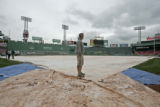 0051 Mike O'Connor with the Fenway Park ground crew gets ready to remove the rain tarp from the...
