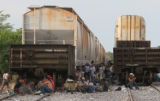 Illegal immigrants, men, women and children from Central America, wait along the train tracks in...