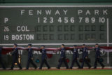 [ROX977] Members of the Air Force carry the United States flag below the Green Monster in left...