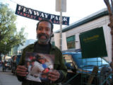 [562] Larry McCord, cq, of Boston sells the Boston Globe newspaper outside Fenway Park before Game...