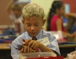Weber second grade student Joseph McGinnis works on putting together his crayon box, Tuesday...
