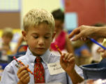 Weber second grade student Joseph McGinnis decides what colors he wants in his crayon box, with...