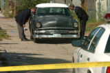 [Denver, CO - Shot on: 8/30/04] Detectives peer inside a car involved at a robbery in the alley...