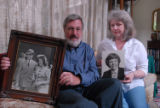 Dennis Nelson and Denise Nelson poses at their Bethesda MD home with 1941 photo of Dennis' parents...