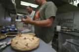 Lance and Lester work together readying pies for presentation. Sheryl and Lester Thorne working at...