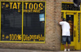 "A man who did not wish to give his name looks into Mr. Tank""s Tattoos on  East Colfax Ave...."