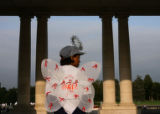 A volunteer angel, Tara Nelson, overlooks a section of the memorial quilt at Cheesman park, as...