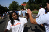 17 year-old Gloria Senoga (cq) cheers people on, as she volunteered to be part of the 20th Annual...