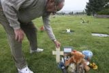 David Crowfoot, Edgewater, Colo. native,  adjusts a cross left at the gravesite where Chandler A....