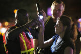 Aurora police officer Everett Williams, left, administers a sobriety test to a driver who was...