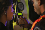 "Aurora police officer Everett Williams, right, administers a ""breathalizer"" test, to..."