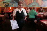 Edith Falasco (cq) 82,  a waitress, delivers a menu and a smile to a customer as she works  the...