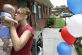 Salina Newman kisses her son, Simon Newman, 4 months, behind her new home at 4403 Lipan St. on...