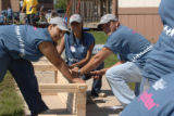 T-Mobile employee volunteers build a picnic bench for Goals, Inc., and Crossroads Alternative...