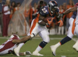 Denver Bronco's running back Andre Hall, right, excapes the grip of Arizona Cardinal's safety Matt...