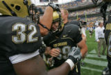 University of Colorado kicker Kevin Eberhart, right, gets a pat on the head from teammate Maurice...