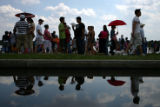 People attending the dragon boat festival are reflected in a puddle left over from Saturday's rain...