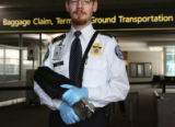 Baggage TSO employee, Nathan Voith (cq) holds a liquid explosive detection device as he poses for...