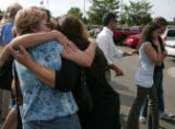 Friends of the Michelle Berra family give Marina Berra (not visable) a group hug outside a...