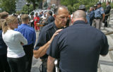 0646 Denver Police Chief Gerry Whitman whispers to a colleague while Governor Bill Ritter...