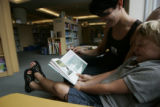 Paris Samuels (cq) of Boulder, Colo., reads to Liam Clevenger, 5, at the Denver Public Library on...