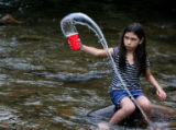 Michaela Sierra,10, plays with a cup in Clear Creek, Wednesday afternoon, July 18, 2007, Idaho...