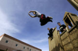 Ryan Ford (cq), right, leaps off a piece of playground equipment while Andy Taber (cq), center,...
