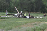 Investigators sift through the wreckage of a WW II-era Beechcraft C-45 lays in a field in SW Weld...