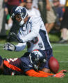 Dre Bly, bottom, breaks up a pass intended for Brian Clark, top, at Broncos training camp at...