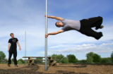 Ryan Ford (cq), right, does a flag on a pole while Andy Taber (cq), left watches as they practice...
