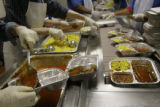 Employees prepare hot meals for the Meals on Wheels program at the Volunteers of America building...