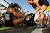(at right) 24 year-old Tailor Goad (cq) helps her teammate, Nancy Stevens (cq), remove the wetsuit...