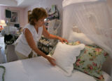 Scarlett Rose owner June Kuzas (cq) adjusts a pillow in her shop in Lafayette, Colo. July 16,...