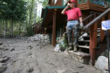 DLM0178  Jack Spencer talks on the phone as he looks at the flow of mud that surrounds his home in...