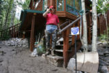 DLM0180  Jack Spencer talks on the phone as he looks at the flow of mud that surrounds his home in...