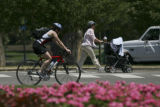 Some unidentified folks walk and ride bikes thru Washington Park in Denver, Colo. on Monday July...