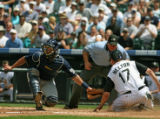 Rockies Todd Helton, right, slides safe at home while Brewers catcher Damian Miller, tries to make...