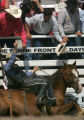 Cowboys try to get the horse ridden by Brad Rudolf to get up after it sat down in the chute in the...