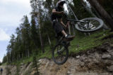 A rider hits a feature in the bike park at Winter Park Resort in Winter Park, Colo., on Monday,...