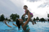 Karina Rodriguez (cq), 13, throws her niece Amara Duran (cq), 2, in the air while beating the heat...
