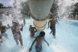 DLM1515  Children run through the water flying in the splash park at the Mestizo Pool at Curtis...