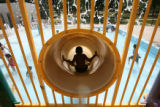DLM1660  A boy swooshes down the slide in the splash park at the Mestizo Pool at Curtis Park  as...