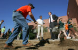 Volunteer Ed Strain (cq), left, shovels dirt for landscaping as Happy Haynes, center left, talks...