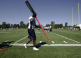 A shoeless Javon Walker lends a hand as he moves the chains  during practice on Thursday of...