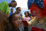 "3 year-old Minnie Burney (Cq) gets a turtle painted on her cheek by ""Rosebud"", the clown..."
